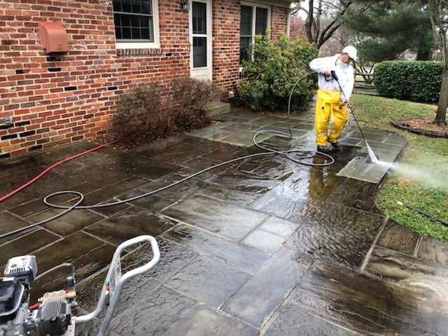 Power washing a concrete patio